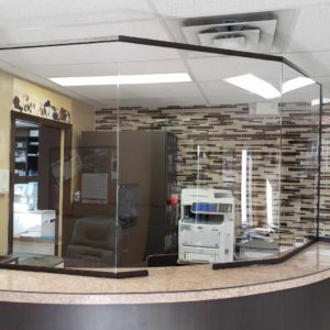 A glass sneeze guard installed in the service desk of an office.